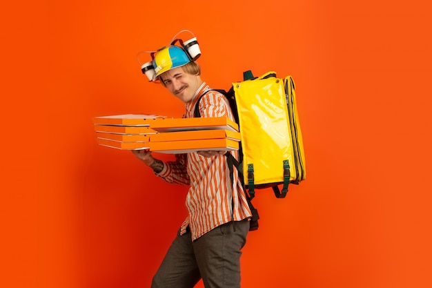 Бесконтактная служба доставки во время карантина. человек доставляет еду и сумки во время изоляции. эмоции доставщика, изолированные на оранжевый