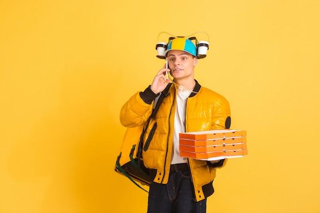 Бесконтактная служба доставки во время карантина. человек доставляет еду и сумки во время изоляции. эмоции доставщика, изолированные на желтом