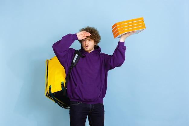 Il servizio di consegna contactless durante la quarantena l'uomo consegna cibo e borse della spesa durante le emozioni di isolamento del fattorino isolato sulla parete blu