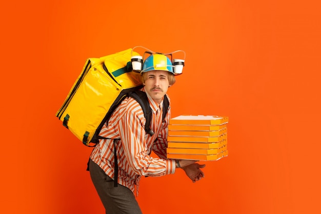 Contacless delivery service during quarantine. man delivers food and shopping bags during insulation. emotions of deliveryman isolated on orange background.