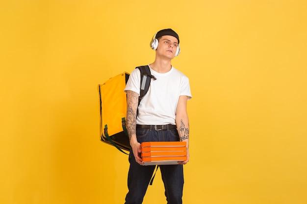 Il servizio di consegna contactless durante la quarantena l'uomo consegna cibo e borse della spesa durante le emozioni di isolamento del fattorino isolato sul muro giallo