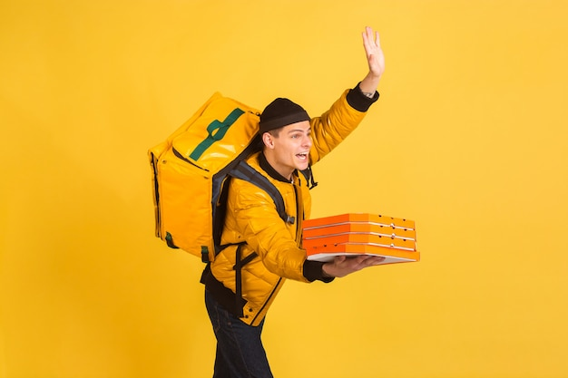 Contacless delivery service during quarantine. man delivers food and shopping bags during insulation. emotions of deliveryman isolated on yellow