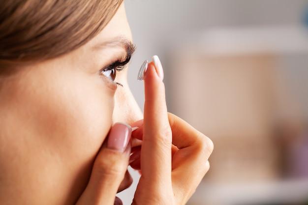 Контактная линза для зрения. молодая женщина надевает оптические линзы дома в комнате