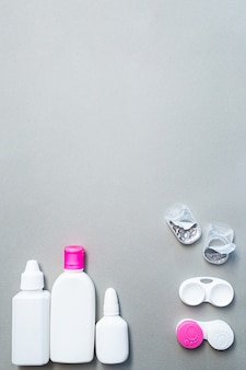 Contact lenses and accessories flat lay on a gray backgroun