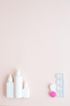 Контактные линзы и средства по уходу за линзами на светло-розовом столе