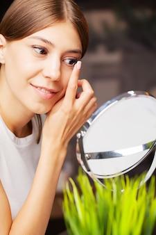 Контактные линзы для зрения. молодая женщина применяет контактные линзы