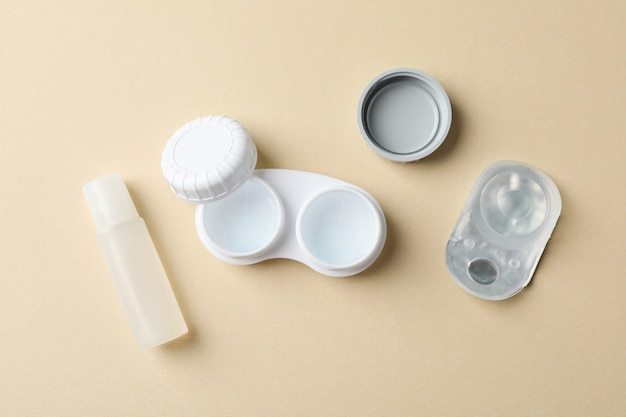 Contact lenses and liquid on beige table, top view