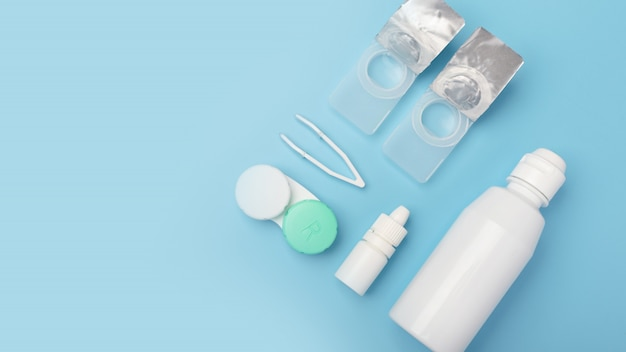 Contact lenses set with saline in bottle, tweezers, eye drops, plastic case with solution