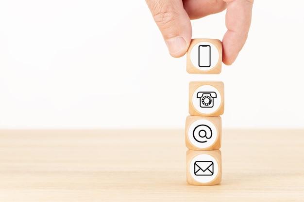 お問い合わせの背景。ウェブサイトのページ。木製のブロックと連絡先アイコンが積み重ねられたブロックを持っている手。スペースをコピーします。