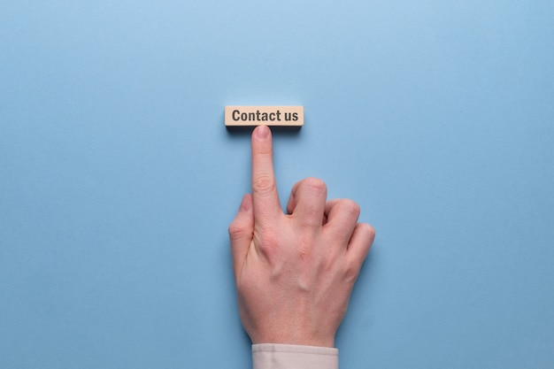 手のテキストと木製のブロックのビジネスコンセプトにお問い合わせください。