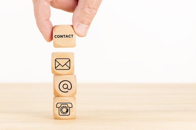 お問い合わせコンセプト。テキストと通信アイコンのサイコロの山と木製のブロックを持っている手。