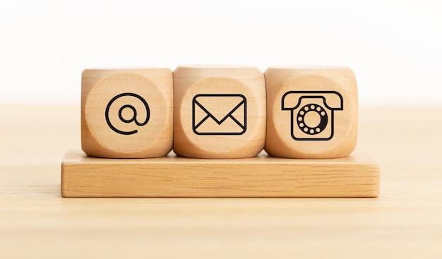 お問い合わせのコンセプト。メール、メール、電話のアイコンが付いた木製のブロック。