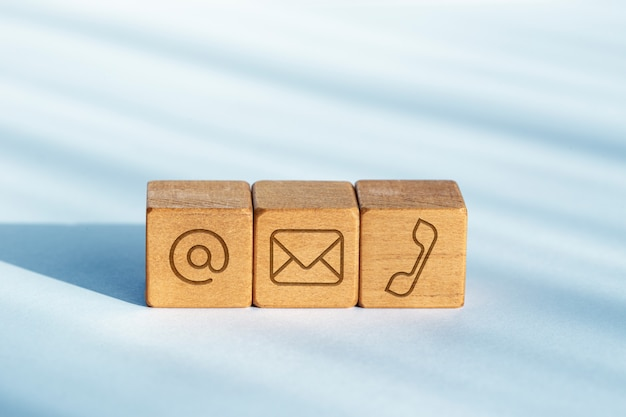 Contact us concept. wooden dices with email, mail and telephone icon