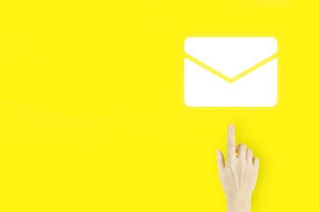 문의 개념입니다. 노란색 배경에 홀로그램 이메일 기호로 가리키는 젊은 여성의 손 손가락. 이메일 및 sms 마케팅 개념입니다.