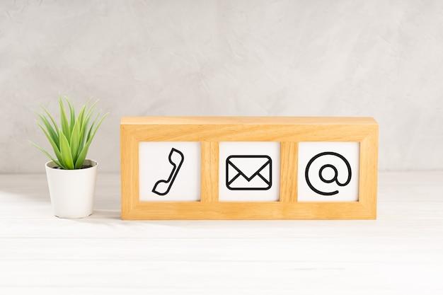Свяжитесь с нами иконки в современной деревянной рамке на столе. белая фактурная стена. копировать пространство