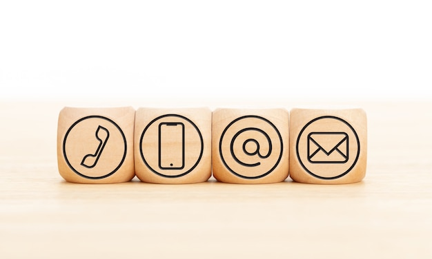Contact us icons in wooden blocks on wooden desk. copy space.