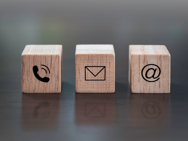 Contact us, marketing and information concept. close up telephone, address and email icon on wooden cube block on dark wooden background.