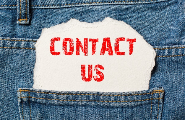 Contact us on white paper in the pocket of blue denim jeans