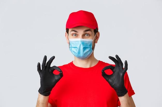 非接触型決済、covid-19、ショッピングのコンセプト。赤いユニフォームを着た陽気で満足のいく宅配便、帽子、手袋付きの医療用マスクは大丈夫、承認または保証のジェスチャーを示し、サービスをお勧めします