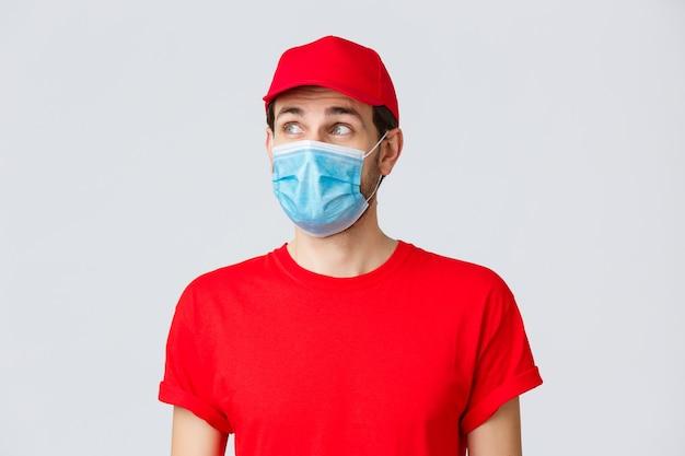 Бесконтактная доставка, covid-19 и концепция покупок. вдумчивый курьер в красной форменной кепке, футболке и медицинской маске с перчатками, смотрит в левый верхний угол, читает баннер или рекламу