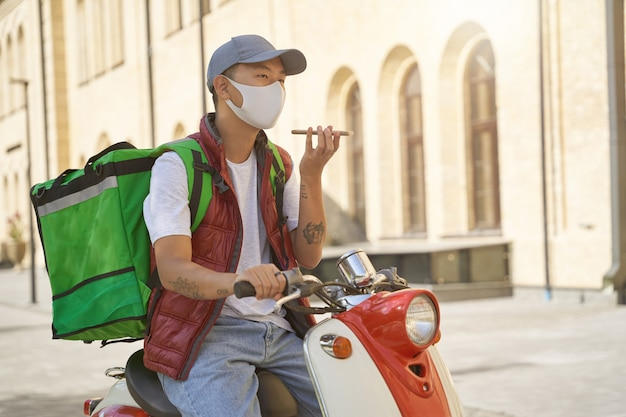 Бесконтактная доставка во время карантина молодой азиатский курьер-мужчина с термосумкой на лице