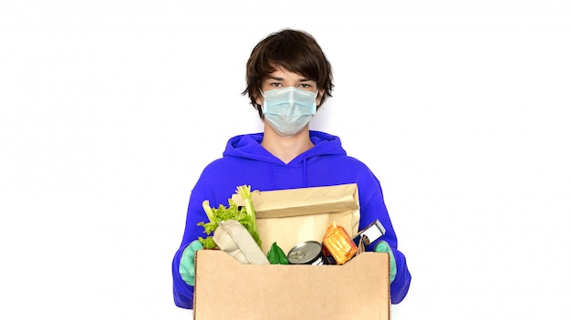 Contactless delivery. a man in a medical mask and gloves holds a box. isolate, copy space. coronavirus isolation online delivery of products and goods, shopping
