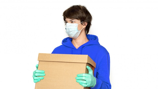 Contactless delivery. a man in a medical mask and gloves holds a box. isolate copy space.
