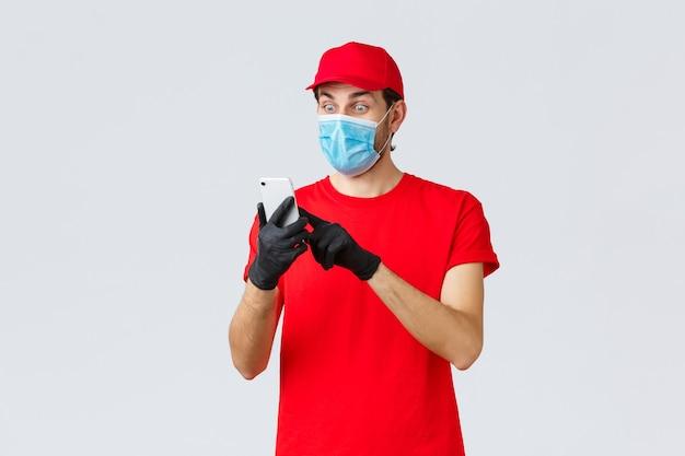 Covid-19、自己検疫中の非接触型配送、支払い、オンラインショッピング。フェイスマスクと手袋で興奮した宅配便、スマートフォンのディスプレイを見て驚いて、注文情報を読んで