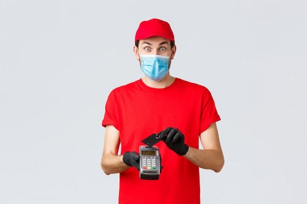 Covid-19、自己検疫中の非接触型配送、支払い、オンラインショッピング。赤いユニフォーム、フェイスマスク、手袋を身に着けた興奮した宅配便、決済端末posでクレジットカードを使用して驚いたように見える