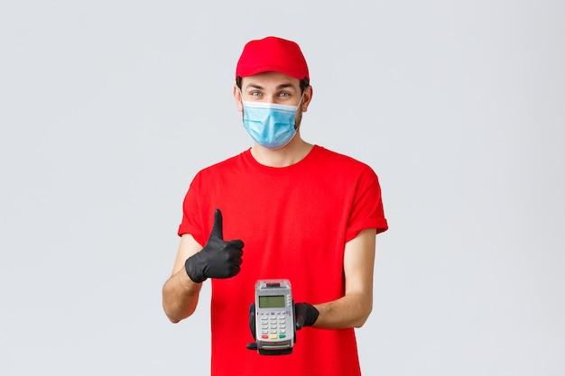 Бесконтактная доставка, оплата и интернет-покупки во время covid-19, самокарантин. приветливый улыбающийся курьер в красной форменной кепке, футболке, медицинской маске и перчатках, оплата заказа через pos-терминал.
