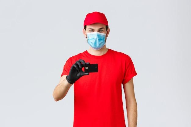 Бесконтактная доставка, оплата и интернет-покупки во время covid-19, самокарантин. красивый курьер в красной форме, кепке, медицинской маске и перчатках, предъявить кредитную карту, заказать в интернете