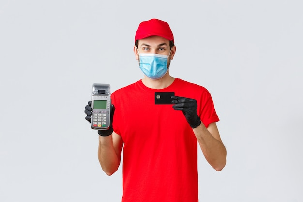 Covid-19、自己検疫中の非接触型配送、支払い、オンラインショッピング。決済端末posとクレジットカードを備えたハンサムな宅配便、安全な支払い注文を提供し、フェイスマスクと手袋を着用します