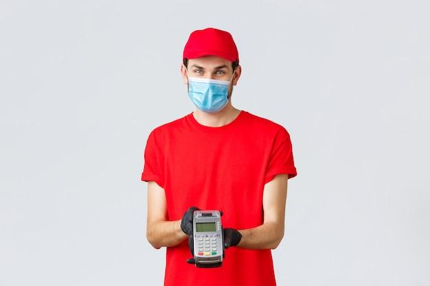 Covid-19、自己検疫中の非接触型配送、支払い、オンラインショッピング。フェイスマスクと手袋をはめた快適な配達人、赤いユニフォームを着て、決済端末に注文の支払いをするposを与える