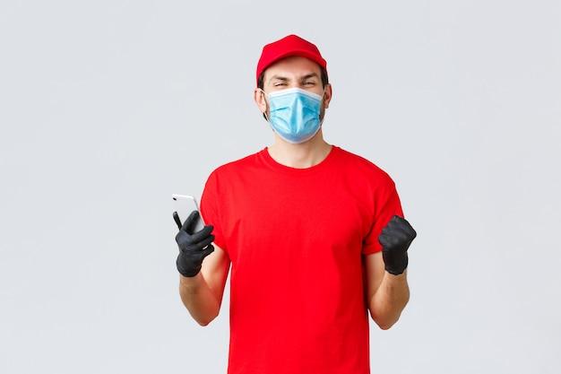 Covid-19、自己検疫中の非接触型配送、支払い、オンラインショッピング。喜んで、赤い制服を着た幸せな宅配便、手袋とマスク、笑顔、アプリケーション、携帯電話で良いニュースを読んでください。