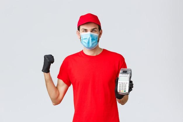 Covid-19、自己検疫中の非接触型配送、支払い、オンラインショッピング。笑顔の宅配便を喜んで、顧客がpos端末とクレジットカード、拳ポンプで注文の支払いをするように促します