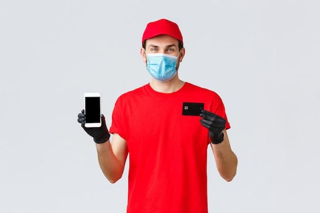 Covid-19、自己検疫中の非接触型配送、支払い、オンラインショッピング。赤い制服を着た笑顔の宅配便、スマートフォンの画面とクレジットカードを示す手袋とフェイスマスク、注文用アプリ