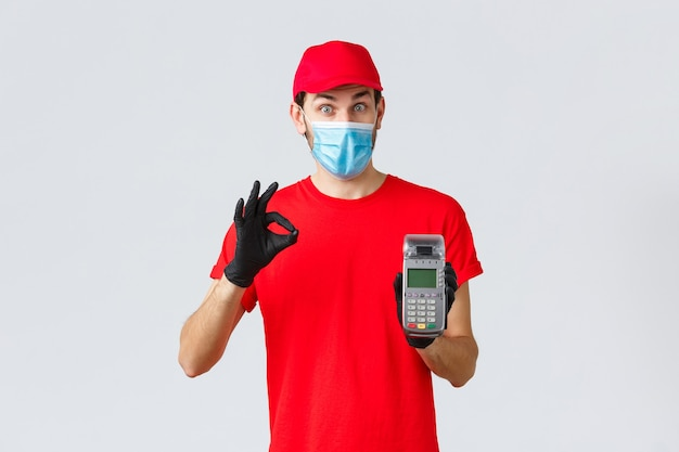 Contactless delivery, payment and online shopping during covid-19, self-quarantine. excited courier in red uniform, face mask and gloves recommend pay order with pos terminal and credit card