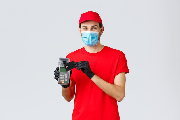 Contactless delivery, payment and online shopping during covid-19, self-quarantine. friendly courier in red uniform, gloves and face mask, showing paying order with pos terminal and credit card