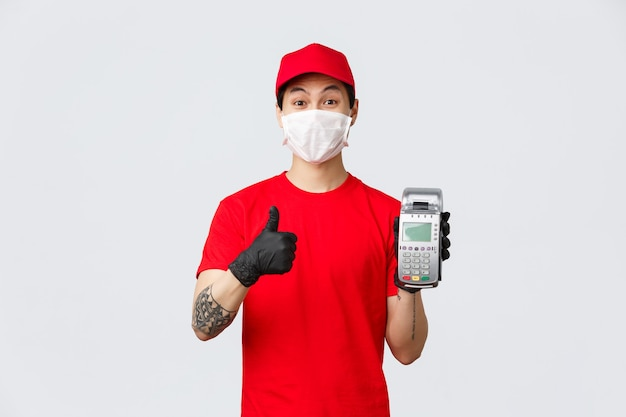 Бесконтактная доставка, безопасная покупка и покупка во время концепции коронавируса. веселый азиатский курьер в медицинской маске и перчатках показывает платежный терминал, показывает палец вверх для использования pos-магазина товаров.