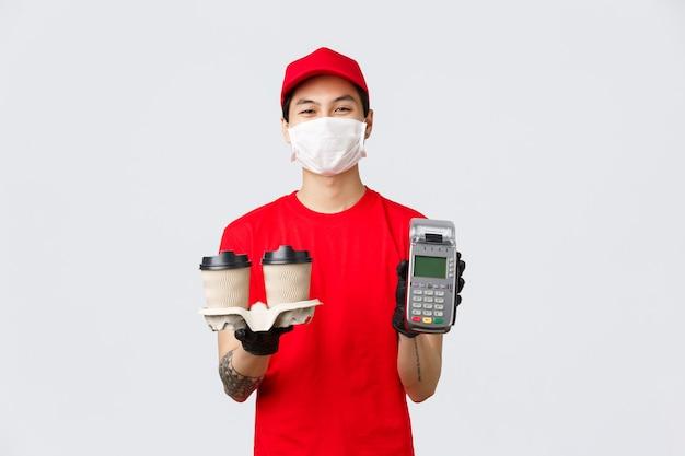 Бесконтактная доставка, безопасная покупка, покупка во время концепции коронавируса. улыбающийся симпатичный курьер в медицинской маске и перчатках, служащий в фаст-фуде, показывает pos-терминал и приносит покупателю кофе