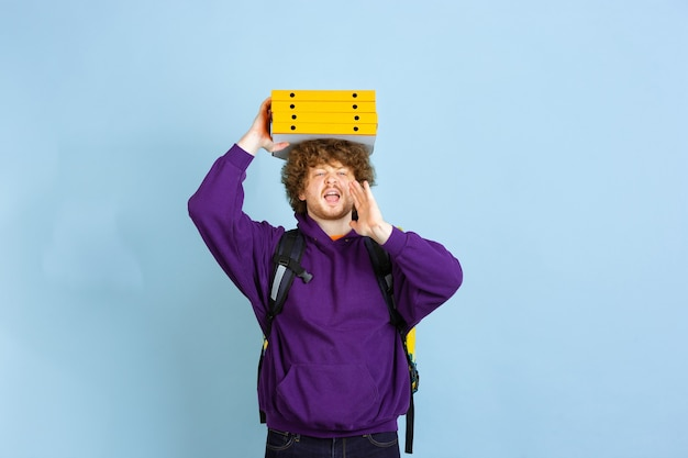 Contactless delivery service.emotions of deliveryman isolated on blue wall