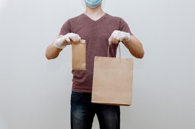 お店やレストランからのマスクされた手袋をした宅配便による非接触型食品配達。