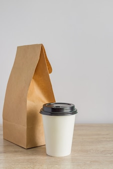 Contactless food delivery during. mockup of dekivery service. empty blank craft paper backage and disposable coffee cup on the table