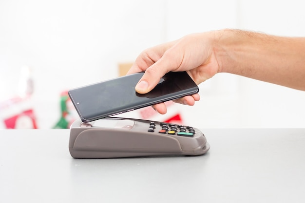 Бесконтактный мобильный платеж. платежный терминал и смартфон в руках