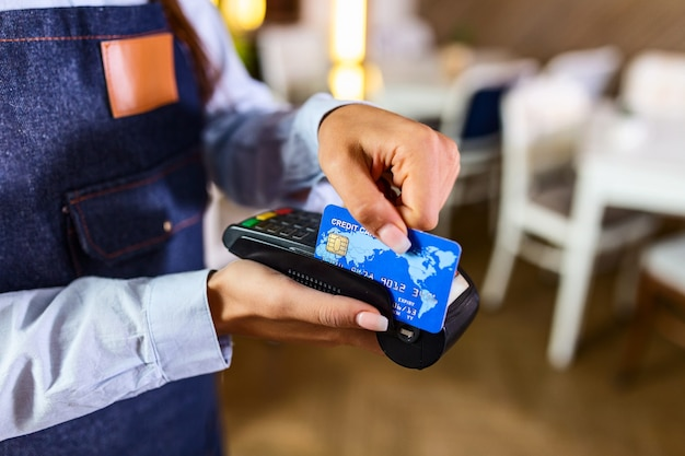 Contactless payment concept, female holding credit card near nfc technology on counter, client make transaction pay bill on terminal rfid cashier machine in restaurant store, close up view