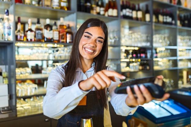 비접촉 결제 개념, 카운터에 여성 지주 터미널 nfc 기술, 클라이언트는 레스토랑 상점의 터미널 rfid 계산대 기계에서 거래 지불 청구서를 작성하고, 뷰를 닫습니다.