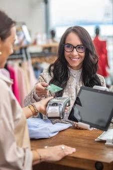 여성 고객이 패션 매장에서 손에 단말기를 들고 있는 점원으로 비접촉식 결제를 하고 있습니다.