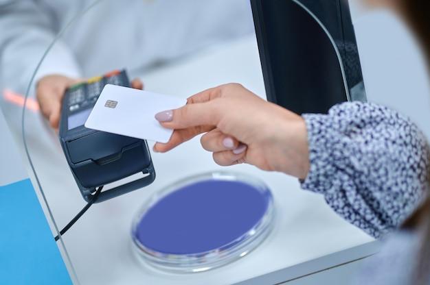 비접촉 결제. 얼굴 없이 금전 등록기 창에 뻗은 pos 터미널에 신용 카드를 가져오는 매니큐어가 있는 우아한 여성 손