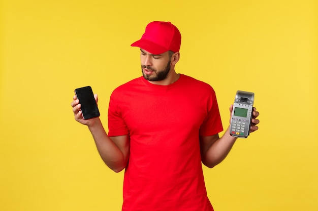 Contactless payment online delivery internet shopping concept curious courier in red uniform cap and...