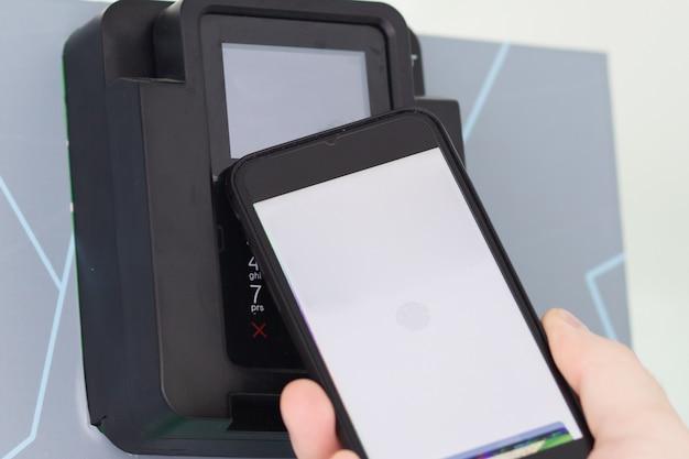 Бесконтактная оплата. рука платит смартфоном по счету в кассовом терминале